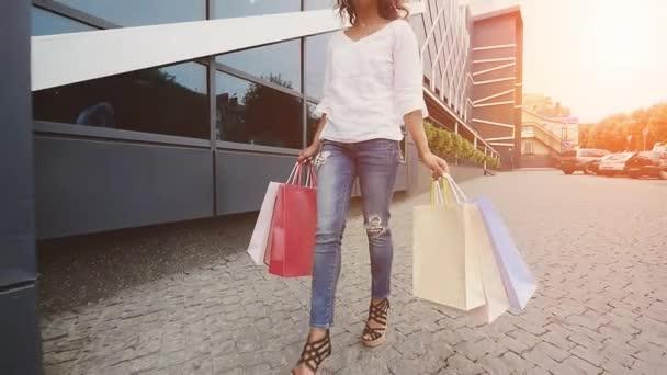 Értékesítés, fogyasztás: magabiztos hölgy bevásárló táskák, séta a városban. Lassú mozgás. Sunshine háttér