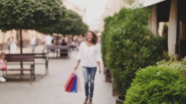 Prodej, konzumerismus: jistý dáma s nákupníma taškama po nakupování čas ve městě