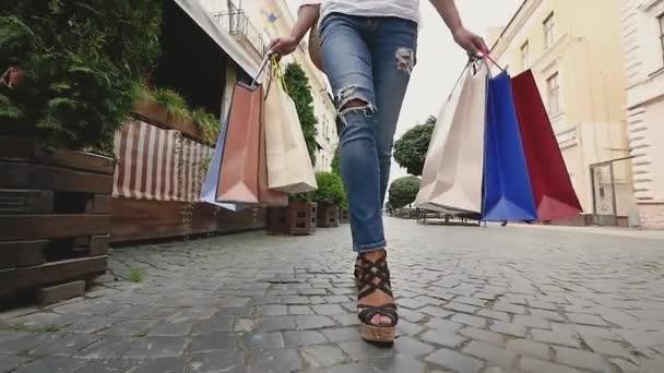 lábak karcsú, fiatal nő, a város bevásárló táskák, lassú mozgás, séta