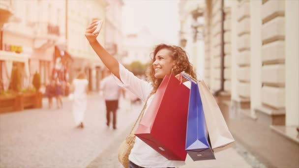 Sale, consumerism: Confident lady with shopping bags make selfie on smartphone. Sunshine background.
