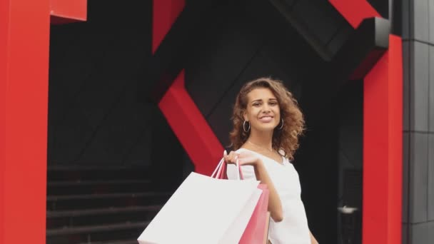 Szép nő, gazdaság bevásárló táskák, és mosolygott. bevásárlóközpont háttér
