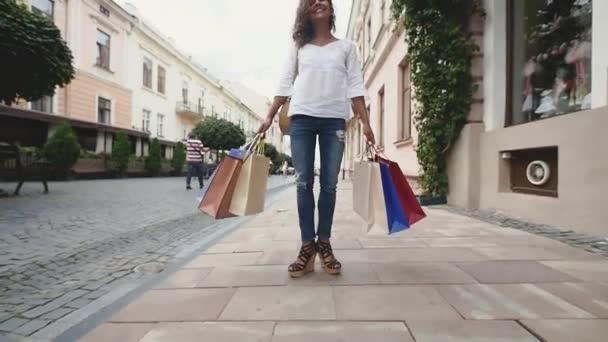 Veselá žena s nákupní tašky ve městě. Zpomalený pohyb. Pohled zdola