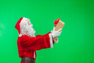 Santa Claus with gift box against chromakey. side view