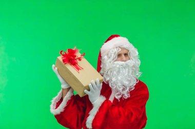 Santa Claus with gift box against chromakey. Santa interesting whats inside box