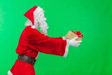 Merry Christmas. Santa Claus in a red suit gives out gifts in boxes on a green screen background chroma key. side view