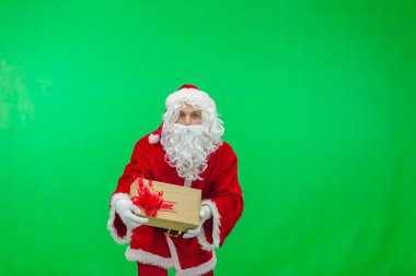 Merry Christmas. Santa Claus in a red suit gives out gifts in boxes on a green screen background chroma key