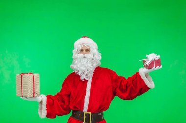 Santa holding two Christmas gifts on green background