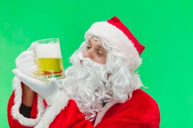 Father Christmas Santa looks at a lovely glass of beer. chroma key. close up