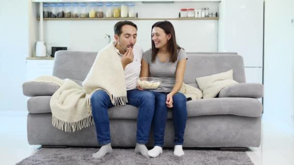 A férj és a feleség ül a kanapén