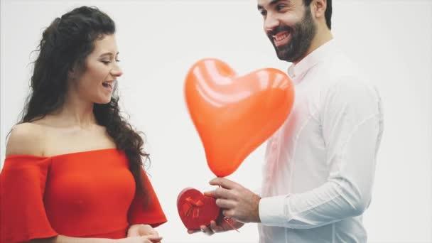 Krásný mladý pár doma. Objímání Kiss a užijte si čas společně. Oslavu Valentýna. Dárková krabice v ruce a balónek v podobě srdce.