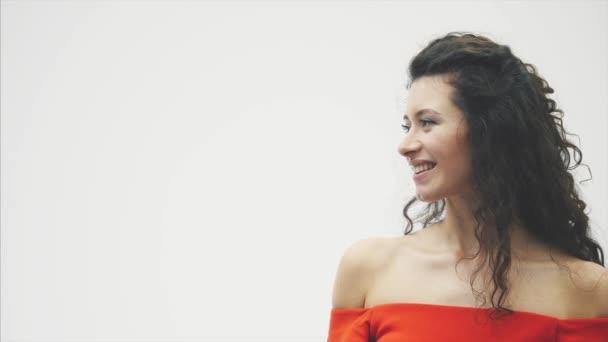 Schöne romantische Paar isoliert auf weißem Hintergrund. Eine attraktive junge Frau tragen rote Rosen in einem Kleid und ein schöner Mann in einem weißen Hemd gibt die Rose mit Liebe und Zärtlichkeit. Valentines