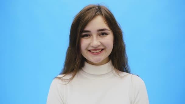 Bella giovane donna con pelle pulita e perfetta. Ritratto di modello di bellezza con trucco naturale e un sorriso. Primo piano sfondo blu, copyspace