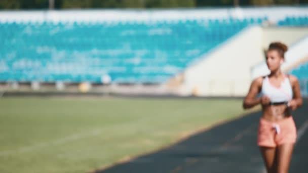 Ritratto di una ragazza forte in abiti sportivi in esecuzione nello stadio. Bella ragazza corre nello stadio e ascolta il giocatore.