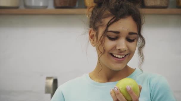 Krásná mladá štíhlá brunetka s zelené jablko v jedné ruce a croissant v druhé ruce na pozadí zeleniny na kuchyňském stole těžké rozhodování mezi zdravou a škodlivých potravin.