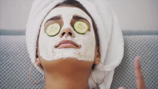 Eine schöne junge Frau bekommt im Kurzentrum eine Gesichtsmaske aufgesetzt, mit Gurken in den Augen. glücklich und macht viel Spaß.
