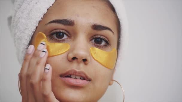 Vértes portréja után fürdő törölköző, fején a gyönyörű nő hozza foltok a szem alatti sötét karikák és ráncok. Fürdőköpeny, vonzó nő teszi kozmetikai kezelések az arcon otthon