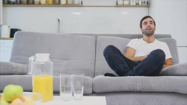 Gyönyörű vidám fiatalember, aki távirányítót. Ezalatt, a TV van néz rövid idő ülő-on dívány otthon.