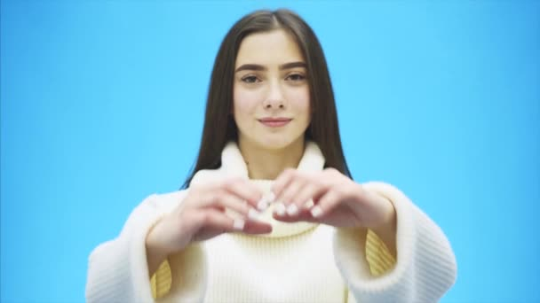 Portrait of a happy young woman wearing a white warm sweater. During this time, a hand gesture of heart shows and feels love. Isolated on a blue background.