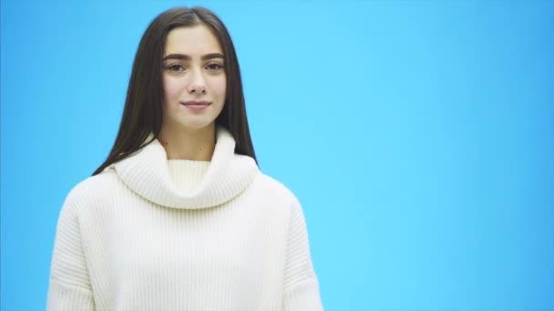 Fiatal csinos lány öltözött fehér ruhák. Ez idő alatt áll a kék háttér. A szeretet szó tartja kezében.