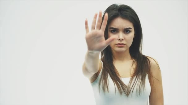 Portrait of a young woman standing with her hands open, showing gesture stops isolated over white background.