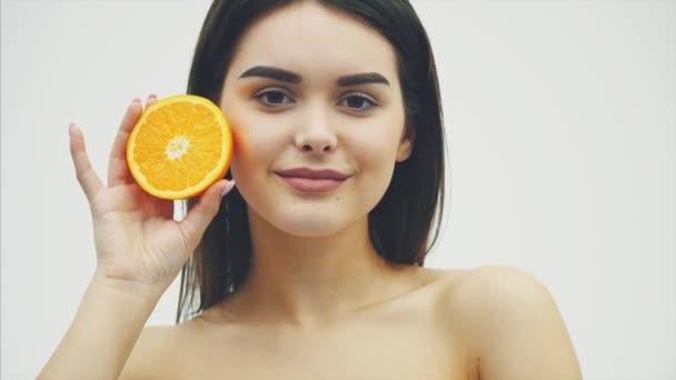 Szép fiatal lány hosszú hajú, tökéletes bőr és smink tökéletes. Tartsa a narancssárga gyümölcs a háttérben, a szem. Fehér háttér.