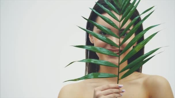 Beautiful young woman with perfect skin and natural makeup posing front of a plant. Tropical green leaves background with fern. SPA, wellness, bodycare and skincare.