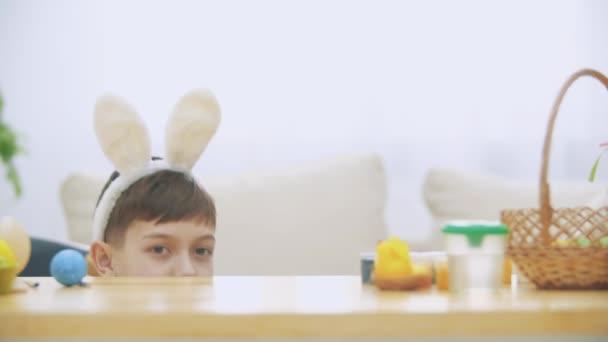 Der süße kleine Junge mit Hasenohren versteckt sich unter dem Tisch voller Osterdekorationen. kleine süße weiße Häschen greift Jungen freundlich an. Lachen steht im Raum.