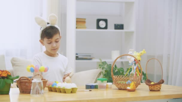 Creative boy is colorizing an Easter egg with a help of paint-brush., wearing bunny ears, then he takes a wooden basket and shows how many coloured Easter eggs there are, and points with his finger