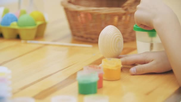 Cute boy is colorizing an Easter egg in an yellow colour with a help of paint-brush. Boy draws an yellow heart.
