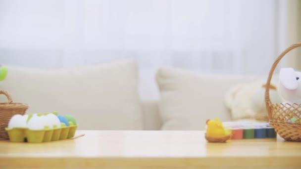 Nettes kleines Mädchen mit Hasenohren versteckt sich unter dem Tisch voller Osterdekorationen. kleines süßes weißes Mädchen schaut belustigt. Lachen steht im Raum.
