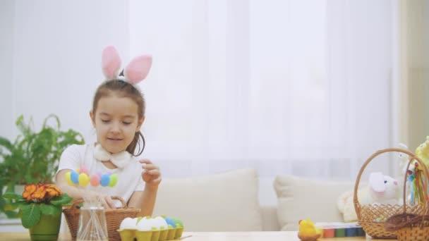 Litle játékos lány, nyuszi füle viselt a fején kiválasztása egy húsvét tojás. Hirtelen valaki észrevette őt. Ő megijedt és elrejtette le.