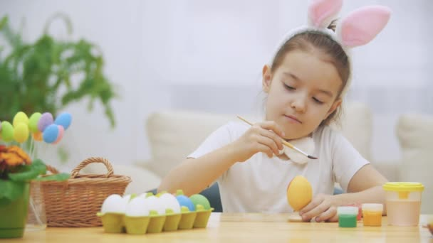 Little playful girl, wearing bunny ears on her head is choosing an a red colour to paint an egg and calmly is painting an Easter egg. Girol has painted an heart on it, then shows a gesture of love.
