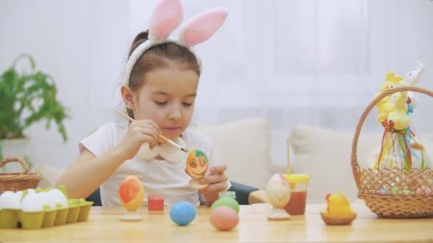 Hravá holčička, nosí na hlavě uši zajíček si vybral oranžovou barvu malovat vajíčka. Dívka je žvýkání a outting žlutá skvrna na nose