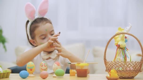 Kis aranyos és imádnivaló lány őszintén mosolyog. Lány mutatja a kéz kis lakásában. Húsvéti ünnep fogalma.