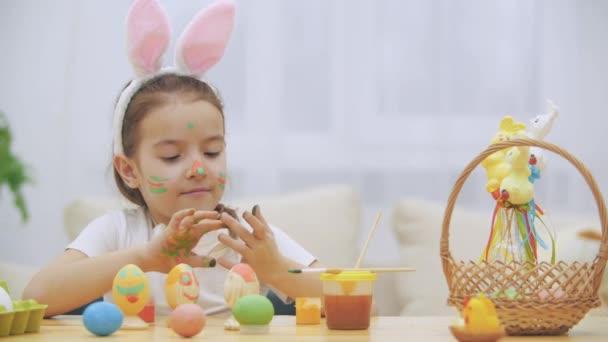 Malé roztomilé a roztomilý dívka je upřímně usmíval. Ona bere velikonoční vajíčko a zobrazuje výsledek její práce ji špinavé barvy rukou. Dívka se chystá vystrašit, v určitém druhu.