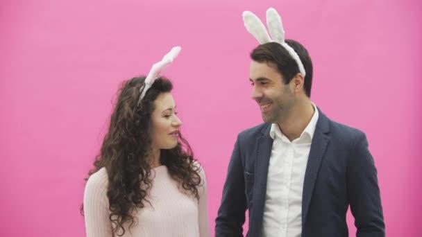 Junges Paar stehend stehend auf rosa Hintergrund. Während dieser Zeit sind sie in Gesindel Ohren gekleidet. Blick auf einander, sprechen und Lächeln.