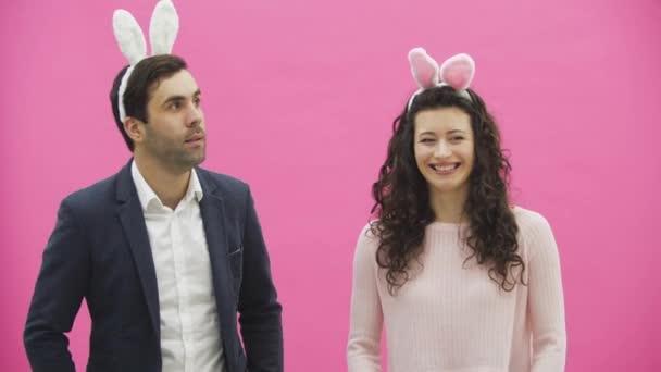 Junges Paar stehend stehend auf rosa Hintergrund. Während dieser Zeit sind sie in Gesindel Ohren gekleidet. Blick auf einander Lächeln aufrichtig