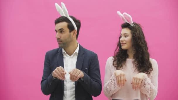 Junges Paar stehend stehend auf rosa Hintergrund. Während dieser Zeit sind sie in Gesindel Ohren gekleidet. Betrachtet man sanft, rhythmisch gleichzeitig den Kopf auf die Seite zu drehen. Ostern.