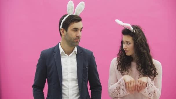 Junge schöne Paar stehend auf einem rosa Hintergrund. Dabei sind sie in Gesindel Ohren gekleidet. Betrachtet man sanft miteinander, in der Liebe.