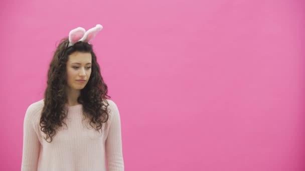 junges schönes Mädchen, das auf einem rosa Hintergrund steht. Das Mädchen bewegt sich wie ein Kaninchen. Sanft in die Kamera blickend, lächelnd.