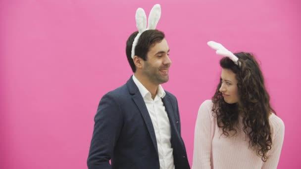 junges Paar steht auf rosa Hintergrund. Dabei führen sie die Bewegung der Kaninchen durch. legte die Frau ihre Hände auf seinen Hals und würgte ihn. Danach lachst du wirklich.