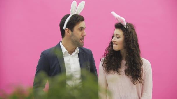 Junges Paar sind schön auf rosa Hintergrund. Während dieser Zeit sind sie in Gesindel Ohren gekleidet. Blick auf einander, Verhalten sich wie die Karnickel, Bewegungen des Mundes und der Zähne zu reproduzieren.