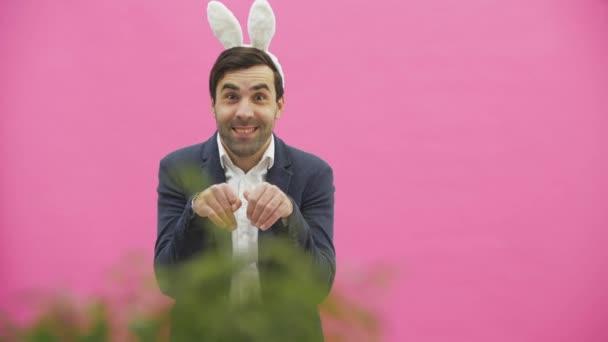 junges Paar sind schön auf rosa Hintergrund. Während dieser Zeit sind sie mit Pöbelohren bekleidet. einander anschauen, sprechen und lächeln, sich benehmen wie Kaninchen.