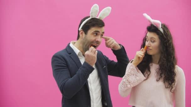 Junges Paar sind schön auf rosa Hintergrund. Während dieser Zeit sind sie in Gesindel Ohren gekleidet. Blick auf einander, spielen sie Karotten, zeigen verschiedene Kaninchen Bewegungen.