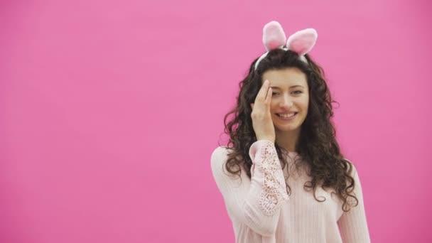 schöne junge Mädchen steht auf einem rosa Hintergrund. Dabei gibt es Hasenohren auf dem Kopf.
