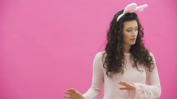 schöne junge Mädchen steht auf einem rosa Hintergrund. Dabei gibt es Hasenohren auf dem Kopf. führt Kaninchen rhythmische Bewegungen mit den Händen eines Rufs aus.