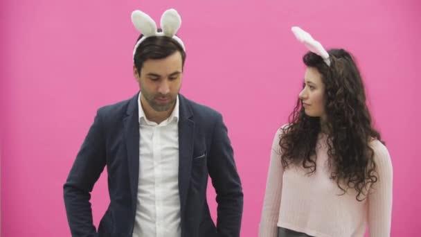 Frisch verliebte Paar auf rosa Hintergrund. Mit abgedroschenen Ohren auf dem Kopf. Dabei sind die Fotos von Sephi am Telefon sehr aufrichtigen Lächeln. Lustige Leute.