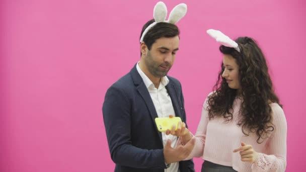 junges Liebespaar auf rosa Hintergrund. mit abgedroschenen Ohren auf dem Kopf. Dabei machen sie am Telefon ein Foto von Sephi, das verschiedene Kaninchenbewegungen zeigt und freuen sich.