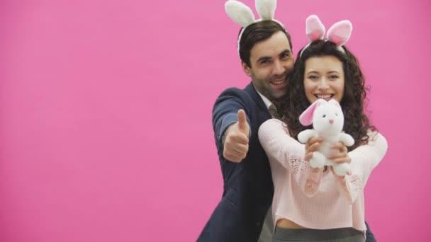 Junge kreative paar auf rosa Hintergrund. Mit abgedroschenen Ohren auf dem Kopf. Dabei hält eine Frau ein Stofftier Hase, ein Mann zeigt eine Klasse. Ein echtes Lächeln geben.