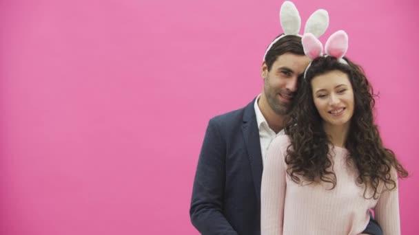 junges kreatives Paar auf rosa Hintergrund. mit abgedroschenen Ohren auf dem Kopf. Dabei zeigen zwei die Gesten der Klasse und schauen sich gemeinsam an.